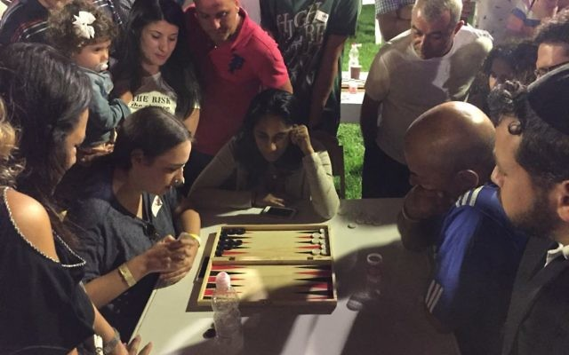 Adi Suchovolsky (left) in action at the Jerusalem Backgammon Championships beneath the Old City Walls on August 24. (Times of Israel staff)