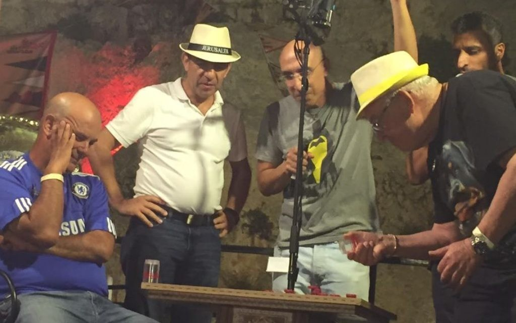 The fateful throw: Itzik Yakobovitch rolls the dice at the Jerusalem Backgammon Championships beneath the Old City Walls on August 24. At left is his rival Gadi Carmeli (Times of Israel staff)