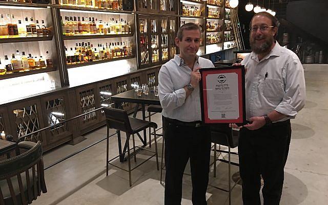 Rabbi Aaron Leibowitz (right), presents an alternative kashrut certificate to the Whiskey Bar Museum in Tel Aviv's Sarona Market (Courtesy Hashgacha Pratit)