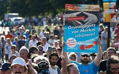 A supporter of the nationalist AfD party holds up a placard which reads 'Protect the constitution from Merkel,' as German Chancellor Angela Merkel speaks at an election campaign rally of her Christian CDU party in Bitterfeld, Germany  on August 29, 2017. (AFP Photo/Odd Andersen)