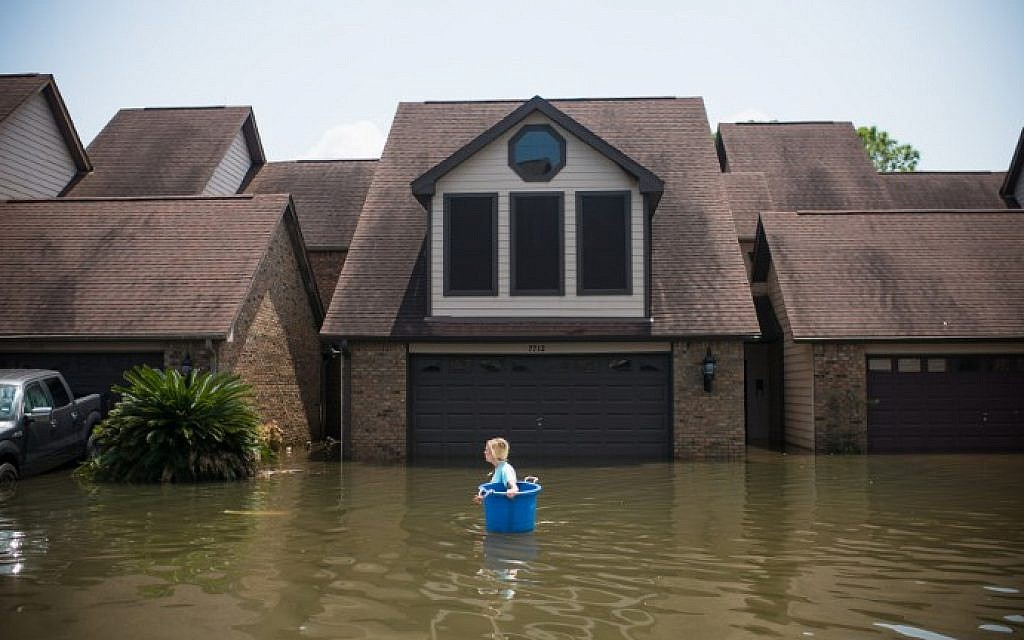 Jenna Fountain carries a bucket down Regency Drive to try to recover items from their flooded home in Port Arthur, Texas, September 1, 2017. (AFP PHOTO/ Emily Kask)