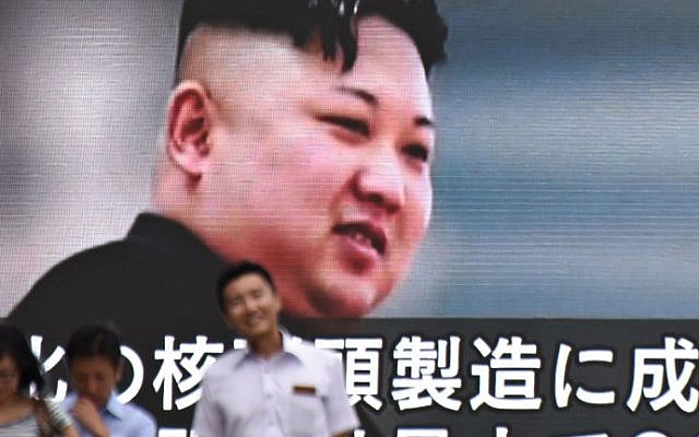 This file photo taken on August 9, 2017, shows pedestrians walking past a huge screen in Tokyo displaying news footage of North Korean leader Kim Jong-Un. (AFP PHOTO / Kazuhiro NOGI)