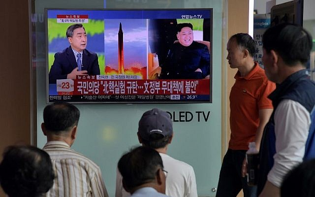 People watch a TV at a train station in Seoul on September 3, 2017, showing a news broadcast about North Korea's latest possible nuclear test. (AFP Photo/Ed Jones)