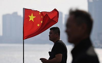 Two Chinese men stand near a Chinese flag as they look out towards North Korea while visiting the Broken Bridge in the Chinese border city of Dandong in China's northeast Liaoning province on September 5, 2017. (AFP / GREG BAKER)