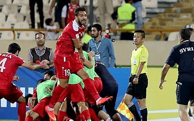 Syria's players celebrate at the end of their FIFA World Cup 2018 qualification football match against Iran at the Azadi Stadium in Tehran on September 5, 2017. (AFP PHOTO / ATTA KENARE)