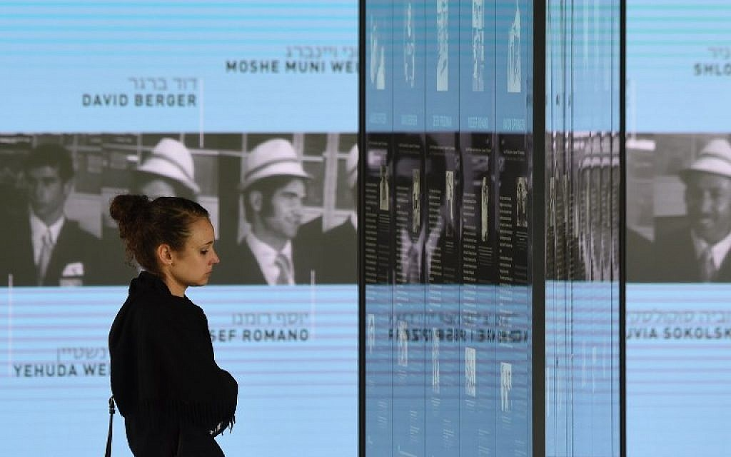 A visitor looks at the portraits of the Israeli athletes murdered at the 1972 Munich Olympics at the Olympic Village displayed inside the Memorial Center on September 6, 2017 in Munich, Germany. (AFP PHOTO / Christof STACHE)