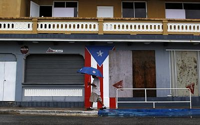 A man with an umbrella walks on a sidewalk as Hurricane Irma approaches in Luquillo, Puerto Rico, on September 6, 2017. (AFP Photo/Ricardo Arduengo)