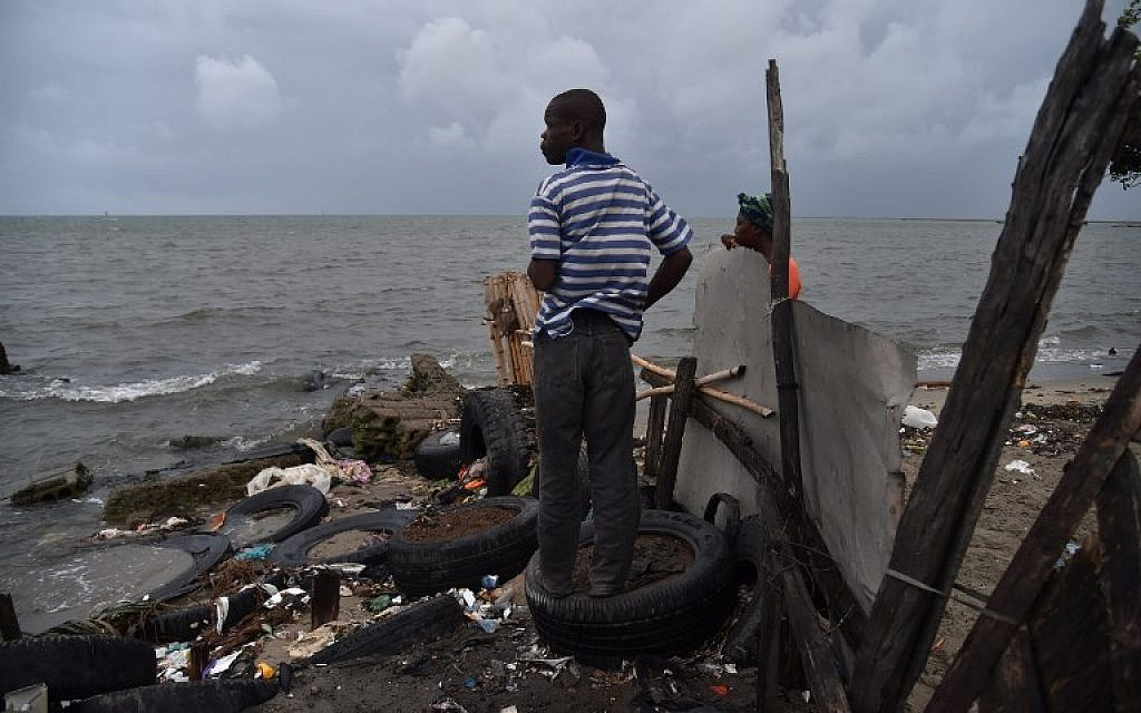 Jean looks at the sea from a house where he is working in the neighborhood of Aviation in Cap-Haitien, Haiti, on September 7, 2017. Hurricane Irma is barreling past Haiti towards the Turks and Caicos Islands, and then the Bahamas. (AFP Photo/Hector Retamal)