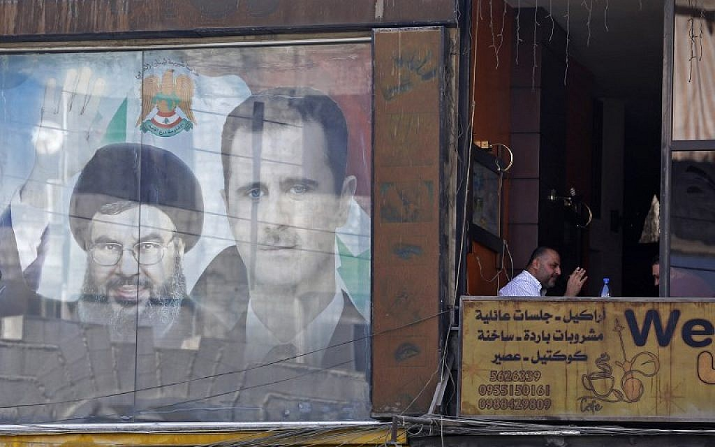 A poster bearing an image of Syrian President Bashar Assad (R) and Hezbollah leader Hassan Nasrallah is seen in Damascus on September 7, 2017. (AFP/Louai Beshara)