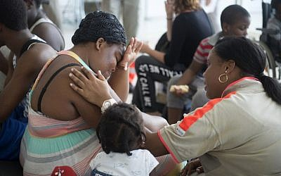 A member of the French Red Cross comforts a woman, who was evacuated from the island of Saint Martin that has been ravaged by Hurricane Irma, upon her arrival on September 9, 2017 at the Pole Caraibes international airport in Pointe-a-Pitre on the French Caribbean island of Guadeloupe.(AFP PHOTO / Helene Valenzuela)