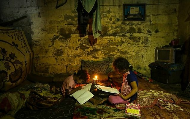 Illustrative: Palestinian children do their homework by candlelight during a power outage in Gaza City on September 11, 2017. (AFP Photo/Mahmud Hams)