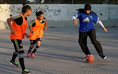 Palestinian sports teacher Rajaa Hamdan (R) leads a football training session with young girls in the northern West Bank village of Deir Jarir, near Ramallah, on September 13, 2017. (AFP PHOTO / ABBAS MOMANI)