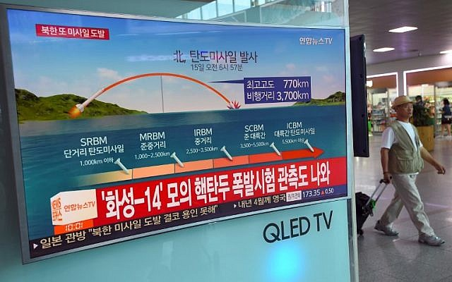 A man walks past a screen showing a news graphic of a North Korean missile launch, at a railway station in Seoul on September 15, 2017. (AFP PHOTO / JUNG Yeon-Je)