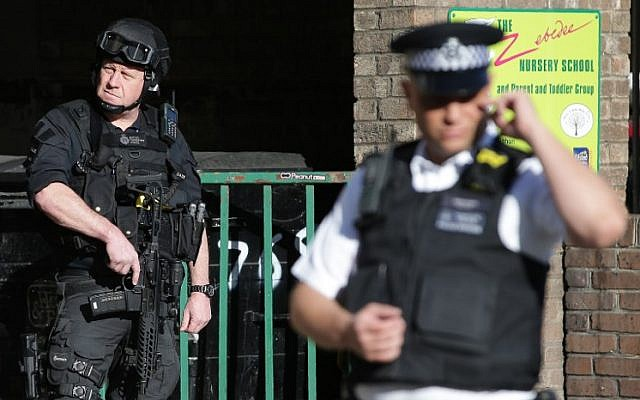 Armed British police officers stand on duty outside Parsons Green underground tube station in west London on September 15, 2017, following a bombing on an underground tube carriage at the station. (AFP/ Daniel LEAL-OLIVAS)