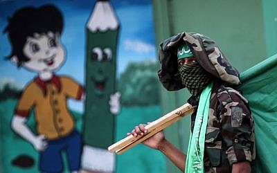 Illustrative: A masked youth cadet from the armed wing of the Hamas terror group carries the movement's flag at a march in the southern Gaza Strip city of Khan Yunis on September 15, 2017.(AFP PHOTO / SAID KHATIB)