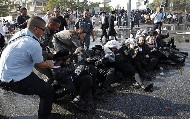 Israeli security forces remove ultra-Orthodox Jewish demonstrators from the road in an ultra-Orthodox neighborhood of Jerusalem on September 17, 2017 as they protest against a court ruling that could require them to serve in the army like their secular counterparts. The demonstration was organised by a particularly hardline group known as Eda Haredit. (AFP PHOTO / Ahmad GHARABLI)