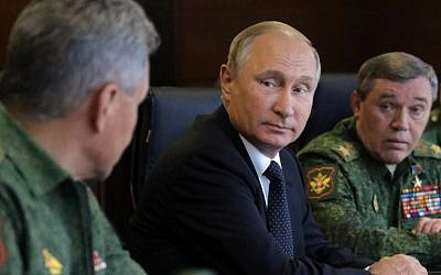Russian President Vladimir Putin (C), accompanied by Defence Minister Sergei Shoigu (L) and Chief of the General Staff Valery Gerasimov (R), watches the joint Zapad-2017 (West-2017) Russian military exercises with Belarus at the Luzhsky training ground in the Leningrad region on September 18, 2017. (AFP/Sputnik/Mikhail Klimentyev)