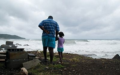 A man and a girl look at the ocean  on September 18, 2017, in Basse-Terre, on the Fench Caribbean island of Guadeloupe, as Hurricane Maria approaches the Caribbean. (AFP PHOTO/Cedrick Isham CALVADOS)
