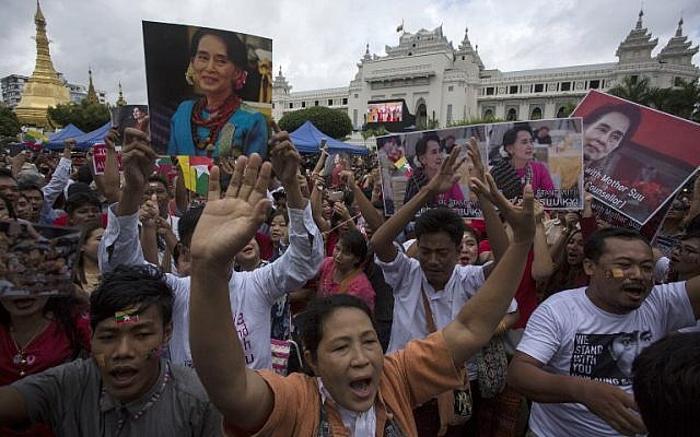 People hold the Myanmar national flag and placards as they attend a public gathering to listen to the live speech of Myanmar's State Counselor Aung San Suu Kyi in front of City Hall in Yangon on September 19, 2017. (AFP PHOTO/AUNG Kyaw Htet)