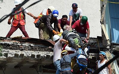 A man is pulled out of the rubble alive following a quake in Mexico City on September 19, 2017.(AFP PHOTO / Ronaldo SCHEMIDT)