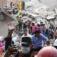 Rescuers, firefighters, policemen, soldiers and volunteers remove rubble and debris from a flattened building in search of survivors after a powerful quake in Mexico City on September 19, 2017. (AFP/Ronaldo Schemidt)
