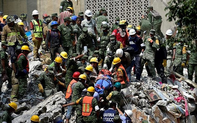 A man is pulled out of the rubble alive in Mexico City on September 20, 2017 as the search for survivors continues a day after a strong quake hit central Mexico. (AFP PHOTO / Pedro PARDO)
