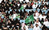 Saudi families sit in a stadium waving national flags at an event in the capital Riyadh on September 23, 2017, commemorating the anniversary of the founding of the kingdom. (AFP PHOTO / Fayez Nureldine)