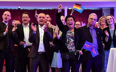 Supporters of the Alternative for Germany party react after exit poll results were broadcast on public television at an election night event in Erfurt, eastern Germany, during the general election on September 24, 2017. (AFP Photo/dpa/Martin Schutt)