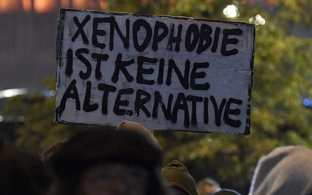 "A protester's sign reads, ""Xenophobia is not an alternative,"" during a protest outside an election night event of the Alternative for Germany (AfD) party in Berlin after the general election on September 24, 2017. (AFP Photo/ John Macdougall)"