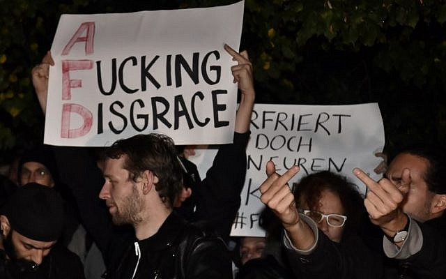 "A protester holds up a sign reading ""A fucking disgrace"" during a protest outside an election night event of the Alternative for Germany (AfD) party in Berlin after the general election on September 24, 2017. AFP/John Macdougall)"