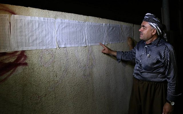 An Iraqi Kurd checks for his name on the voting lists posted outside a polling station in Irbil, the capital of the autonomous Kurdish region of northern Iraq, on the eve on the Kurdish independence referendum, September 24, 2017. (AFP/SAFIN HAMED)