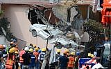 A flattened car is extracted from the rubble of a collapsed building in the Roma Norte neighborhood in Mexico City, September 24, 2017. (AFP/LUIS PEREZ)