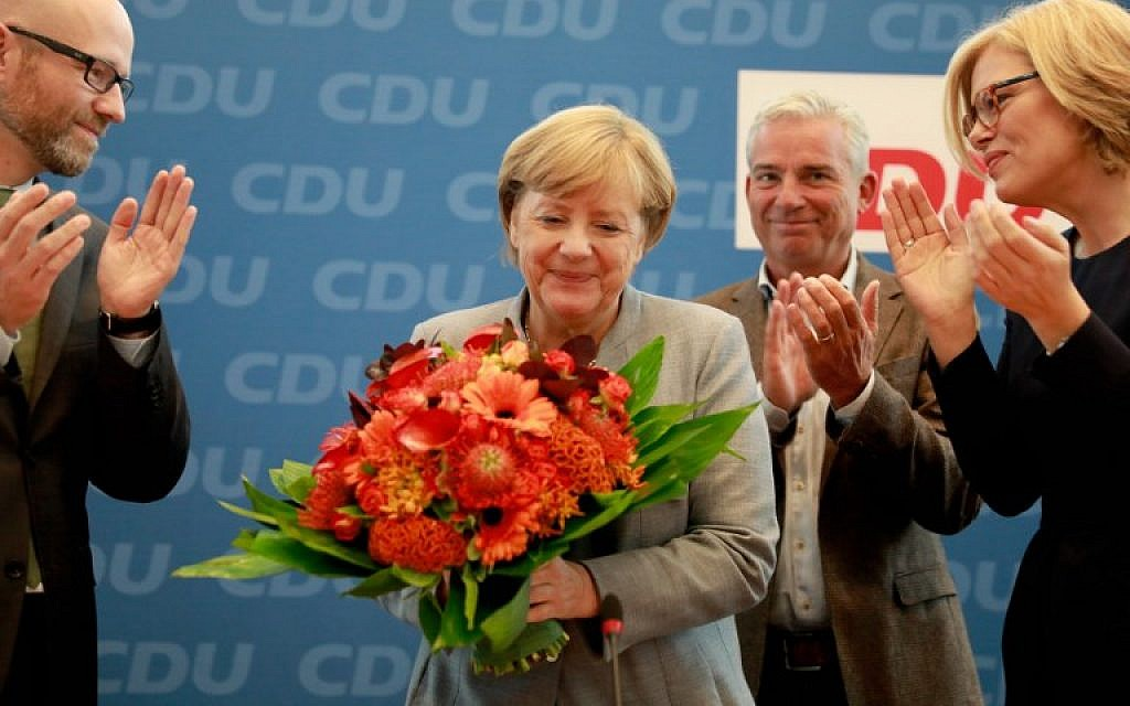 German Chancellor Angela Merkel (2nd L) holds a bouquet of flowers as she is applauded by members of the CDU as she arrives for a meeting with the party's leadership in Berlin on September 25, 2016. (AFP Photo/Odd Andersen)