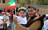 An Iraqi Kurdish man poses as he carries a child wearing the Kurdish flag on his head during a celebration in the northern city of Kirkuk on September 25, 2017, as Iraqi Kurds vote in a referendum on independence. (AFP Photo/Ahmad Al-Rubaye)