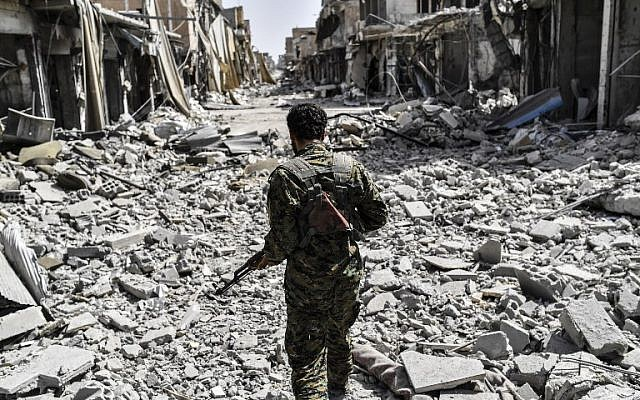 A member of the Syrian Democratic Forces (SDF) sprints through the debris in the old city center on the eastern frontline of Raqqa on September 25, 2017. (AFP PHOTO/BULENT KILIC)