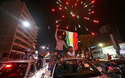 Iraqi Kurds wave the Kurdish flag as they celebrate in the streets of the northern city of Irbil on September 25, 2017, following a referendum on independence. (AFP/Safin Hamed)