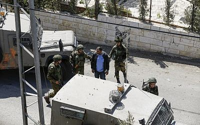 A picture taken on September 26, 2017 in the West Bank village of Bayt Surik shows Israeli soldiers arresting a Palestinian, reportedly the brother of the terrorist who killed three Israelis in Har Adar. (AFP PHOTO / ABBAS MOMANI)