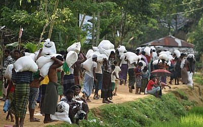 Rohingya Muslim refugees carry food distributed by the Bangladeshi army at the Balukhali refugee camp near Gumdhum on September 26, 2017. (AFP/Dominique Faget)