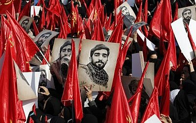 Mourners raise portraits of Mohsen Hojaji, a young member of Iran's elite revolutionary guards Corps (IRGC) who was beheaded in Syria by Islamic State (IS) group fighters, during a funerary procession for him at Imam Hossein Square in the capital Tehran on September 27, 2017. (AFP PHOTO / ATTA KENARE)