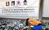 """This file photo taken on March 25, 2012 in Toulouse, southwestern France shows France's Jewish scout placing flowers under a banner paying tribute to the victims of jihadist Mohammed Merah who killed three children and a teacher at the """"Ozar Hatorah"""" Jewish school. (AFP / ERIC CABANIS)"""