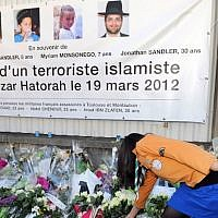 "This file photo taken on March 25, 2012 in Toulouse, southwestern France shows France's Jewish scout placing flowers under a banner paying tribute to the victims of jihadist Mohammed Merah who killed three children and a teacher at the ""Ozar Hatorah"" Jewish school. (AFP / ERIC CABANIS)"