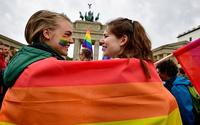 This file photo taken on June 30, 2017, shows two young women wrapped into a rainbow flag at a rally of gays and lesbians in front of the Brandenburg Gate in Berlin. (AFP Photo/Tobias Schwarz)