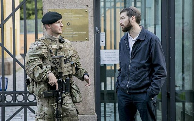 Rabbi Jair Melchior (R) talks to a Danish soldier guarding the Jewish Synagogue in Copenhagen, Denmark, on September 29, 2017.  Danish soldiers took to the streets of Copenhagen for the first time on Friday, September 29, 2017, replacing the police to protect the synagogue and the Israeli embassy which have been guarded ever since two deadly 2015 attacks. (AFP PHOTO / SCANPIX DENMARK / Nikolai Linares)