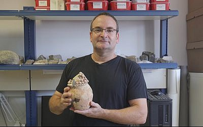 Haifa University Prof. Danny Rosenberg holds the 7,200-year-old model clay grain silo found at Tel Tsaf in the Jordan Valley. (Haifa University)
