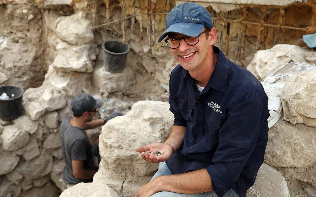 Israel Antiquities Authority' Dr. Joel Uziel holds a collection of First Temple period bullae (sealings) at Jerusalem's City of David, August 2017. (Eliyahu Yanai, City of David)