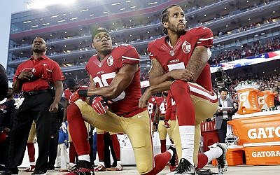 Int his Monday, September 12, 2016, file photo, San Francisco 49ers safety Eric Reid (L) and quarterback Colin Kaepernick (R) kneel during the national anthem before an NFL football game against the Los Angeles Rams in Santa Clara, California. (AP Photo/Marcio Jose Sanchez)
