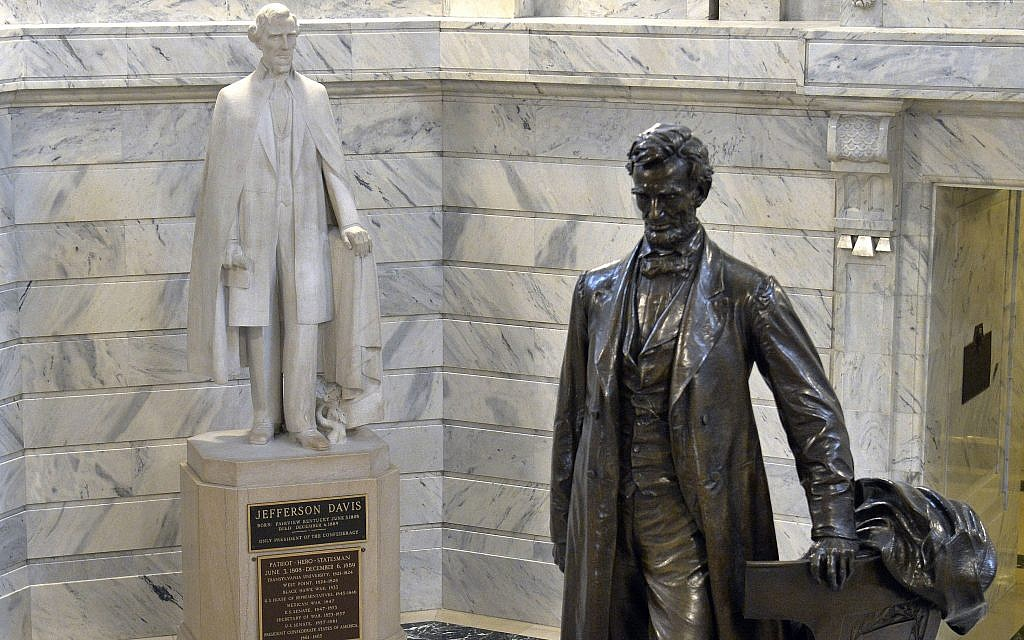 In this Wednesday, Aug. 5, 2015 file photo, a statue of Jefferson Davis, left, looks towards a statue of Abraham Lincoln in the Rotunda of the Kentucky State Capitol in Frankfort, Ky. (AP Photo/Timothy D. Easley)