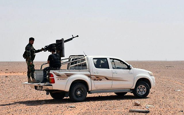 This photo released on Monday, Sept 4, 2017 by the Syrian official news agency SANA, shows Syrian troops and pro-government gunmen standing on pickup trucks with heavy machine-guns mounted on them, in the eastern city of Deir el-Zour, Syria. (SANA via AP)