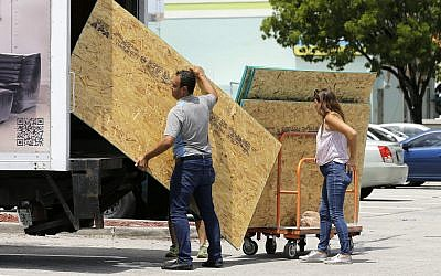 Residents load sheets of strand board on a truck as they prepare for Hurricane Irma, September 5, 2017, in Hialeah, Florida. (AP Photo/Alan Diaz)