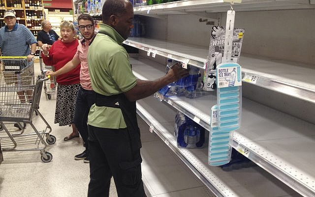 An employee restocks bottled water on bare shelves as customers look on at a Publix grocery store, September 5, 2017, in Surfside, Florida. (AP Photo/Wilfredo Lee)
